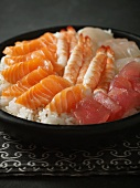Rice, fish and seafood as ingredients for sushi in a bowl