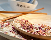 Dried flower petals and rise in a wooden bowl