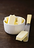 Pieces of butter in a small bowl and on a knife