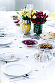 A festively laid table with bunches of flowers, anti-pasti platters and a silver bread bowl
