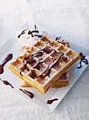 Waffles with chocolate sauce and icing sugar
