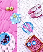 Shoes, cherries, a picnic basket, apples, napkins and cutlery on a picnic blanket