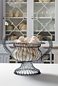 White Eggs in a Wire Basket on Kitchen Table