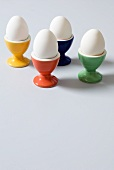 Four White Hard Boiled Eggs in Colorful Egg Cups