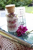 Dekokissen mit gehäkeltem Bezug, Bücher, Rosen-Badesalz, ein Glas und eine Rose