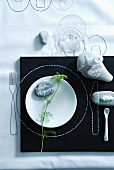 Place setting for summer party: decorative fennel and labelled pebbles, candle and salt on pebbles, outlines of cutlery and plate