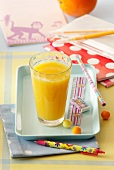 A glass of orange juice and a small tray with school things
