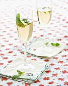 Glasses of champagne with mint leaves on a floral tablecloth