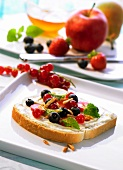 A slice of buttered bread topped with fruit and slivered almonds