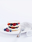 A tower of waffles with berries and cream