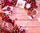 Various strawberry deserts, fresh strawberries and roses forming a frame