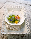 Wild herb salad with edible flowers and cream cheese balls