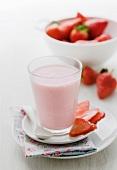 A glass of strawberry milkshake and fresh strawberries