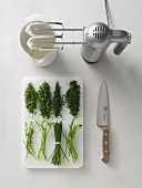 Chopped herbs on a chopping board, whipped cream and a mixer