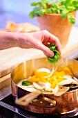 Basilikum in eine Pfanne mit Paprika und Zwiebel geben