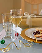 A glass of white wine and snacks on a table laid for Christmas dinner