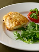 Fish fillet with rocket and an oven roasted tomato
