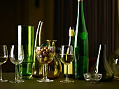 White wine glasses, wine bottles, carafes and olives