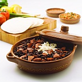 Black Beans and Beef in a Pottery Dish; Tortillas and Salsa