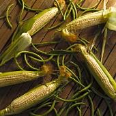 Maiskolben und grüne Bohnen auf Holzuntergrund