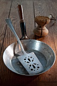 An old frying pan, a fish slice and a meat tenderiser