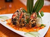 Tuna and Salmon Tempura Seaweed Wraps in a Sesame Sauce on a White Plate