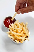 Chips being dipped into ketchup