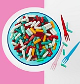 Lots of colourful tablets on a plate with plastic forks next to it