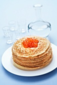 A stack of blinis with salmon caviar and vodka