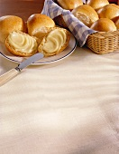 Dinner Rolls in a Basket; Some on a Plate with Butter