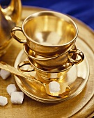 Gold Tea Cups, Saucers and Spoon; With Sugar Cubes