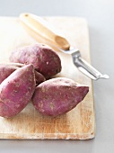 Sweet potatoes on a chopping board with a peeler