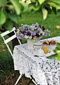 A table set for breakfast with a bouquet of flowers in a garden