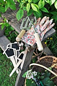 Gardening tools and work gloves on rustic wooden stool in garden