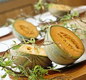 A halved melon decorated with twigs on a table