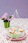 Four cucpcakes in a metal basket