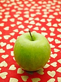 A green apples on a red surface patterned with hearts
