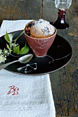 A ceramic cup with miniature Christmas cake on a white monogrammed cloth
