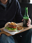 A steak burger with onion rings and a bottle of beer on a wooden board