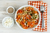 Carrot and spelt spaghetti with sheep's cheese, sesame seeds and parsley