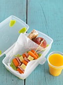 A school lunchbox with carrot kebabs and orange juice