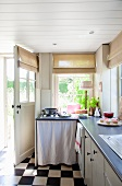 Country-style kitchen with base units and chequered floor