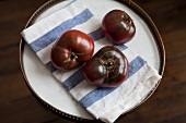 Three Heirloom Tomatoes on a Tray with Dish Cloth
