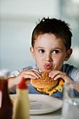A little boy eating a cheeseburger