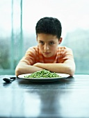 A boy sitting in front of a plate of peas