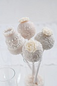Four cake pops in a champagne glass for a wedding