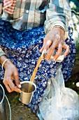 A tea picker drinking tea (Kerala, India)