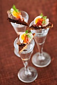 Canapés with herring tartar on vodka glasses