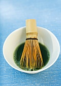 Bowl of macha tea and tea whisk