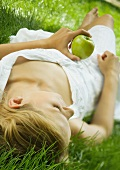 Young woman lying in grass, holding apple